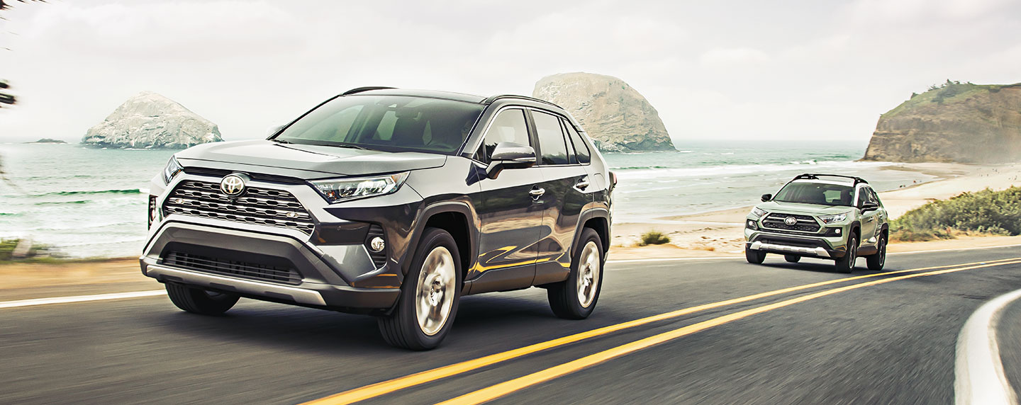 Toyota RAV4 driving on a coastal road.