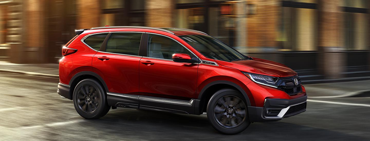 view of red 2020 Honda CR-V driving in the city