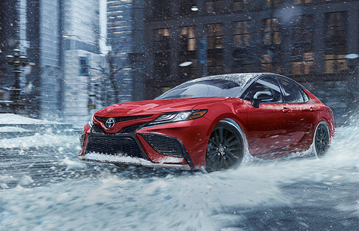 2021 red Toyota Camry driving through the snow downtown
