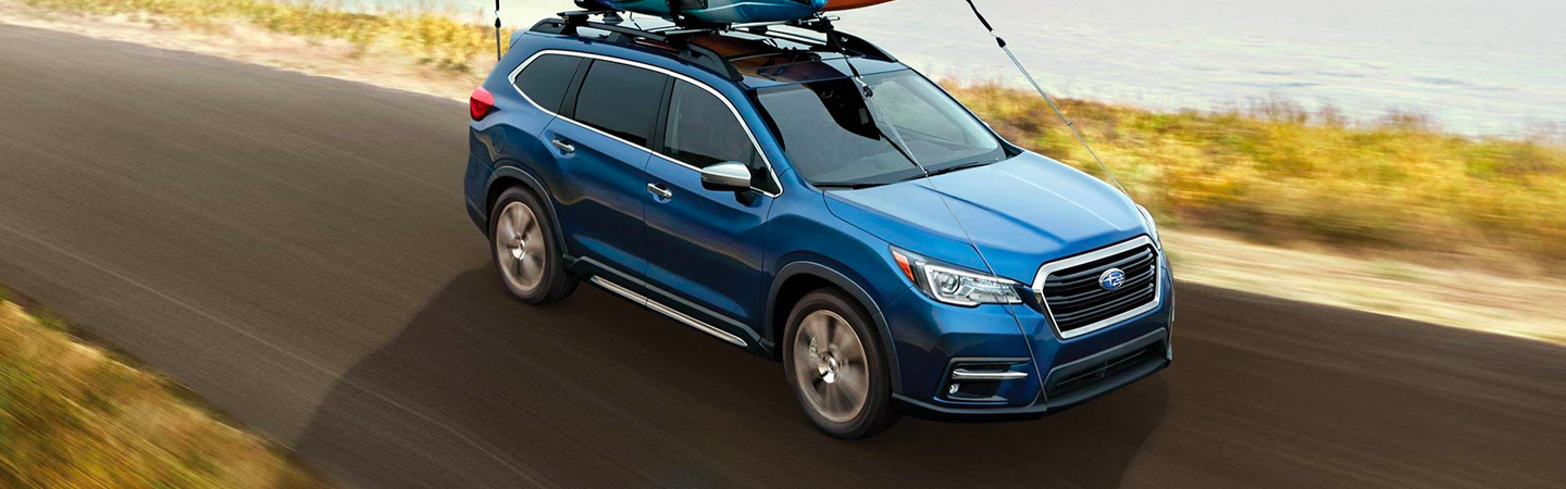 Blue Subaru Ascent driving next to a lake