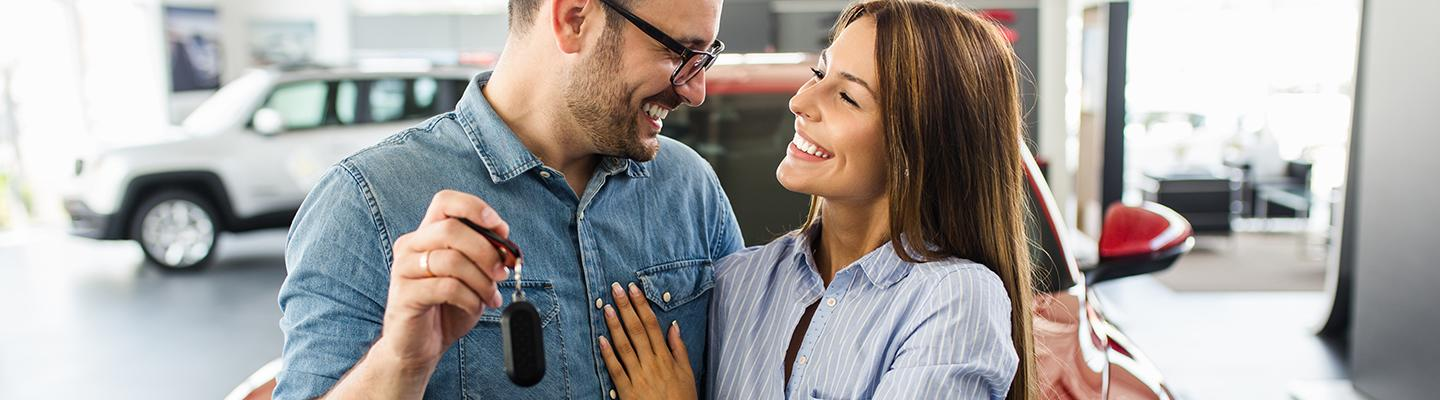 Happy couple holding keys to their new car