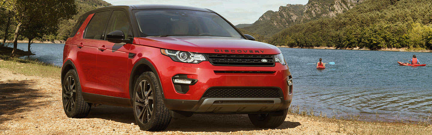 Red Land Rover Discovery Sport parked by a lake