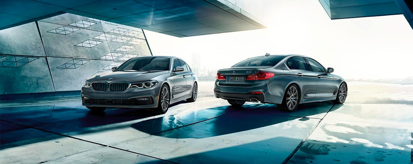 Two BMW 5 series cars parked