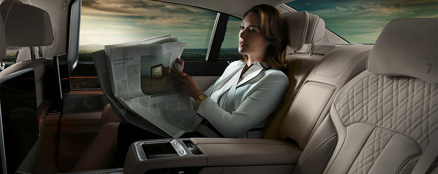 Women reading a newpaper in the back of the BMW 7 series