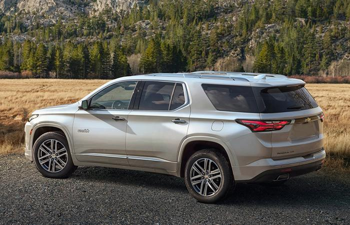 Side profile of a silver Chevy Traverse parked near a mountain range
