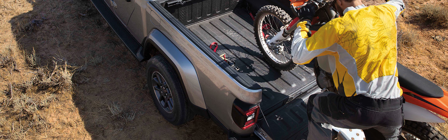 Man loading a dirt bike into the bed of a Jeep Gladiator