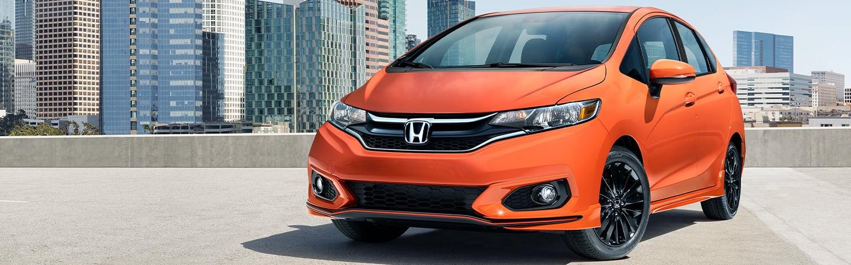 Orange Honda Fit front driver profile view