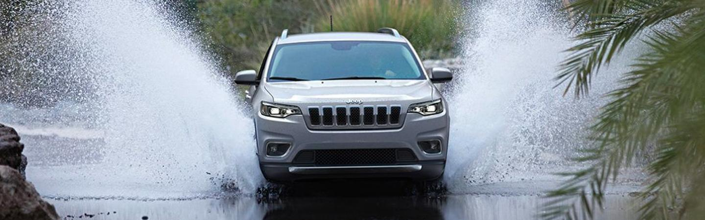 Front view of a 2020 Jeep Cherokee driving through water