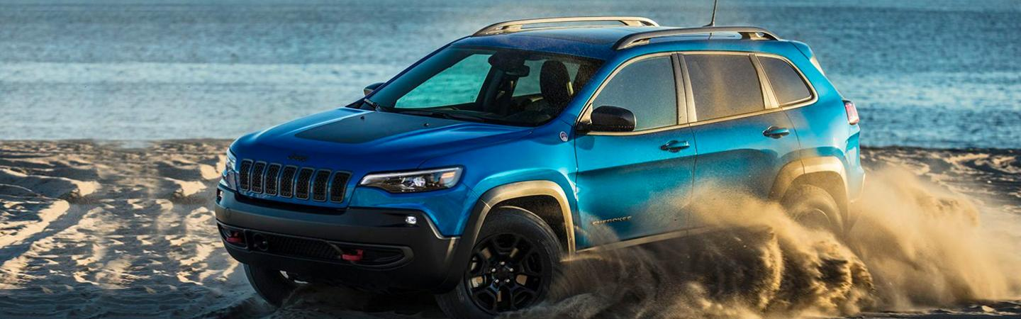 Side view of a blue 2020 Jeep Cherokee turning through beach sand