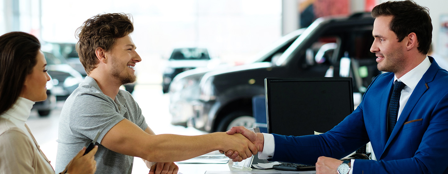 Image of a couple shaking hands and making a financing deal on a new INFINITI for the Bob Moore INFINITI dealership in Oklahoma