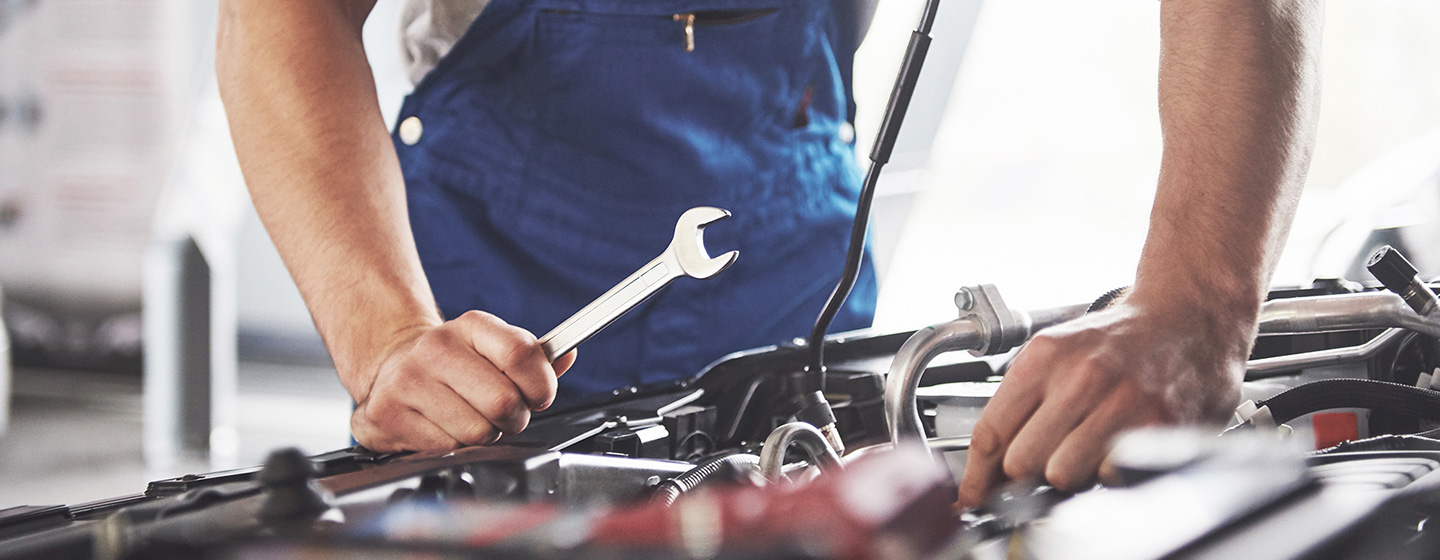 Image of a mechanic looking under the hood of an INFINITI for the service section on the homepage of the Bob Moore INFINITI dealership in Oklahoma
