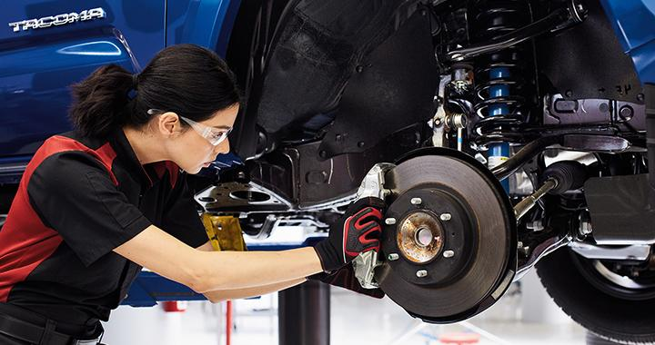 A technician working on a vehicle's brake pads