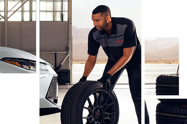 A technician rolling a new tire towards a car