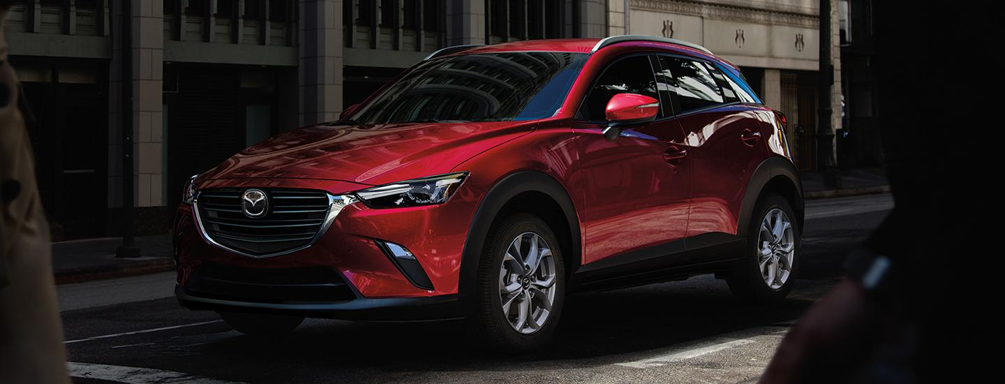 Angled profile of a red Mazda CX-3 parked at an intersection