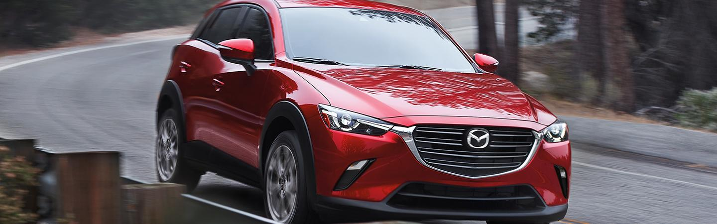 Angled profile of a red Mazda CX-3 in motion
