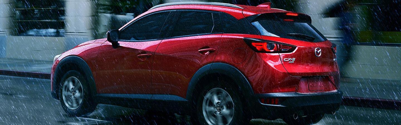 Side profile of a red Mazda CX-3 driving in rain