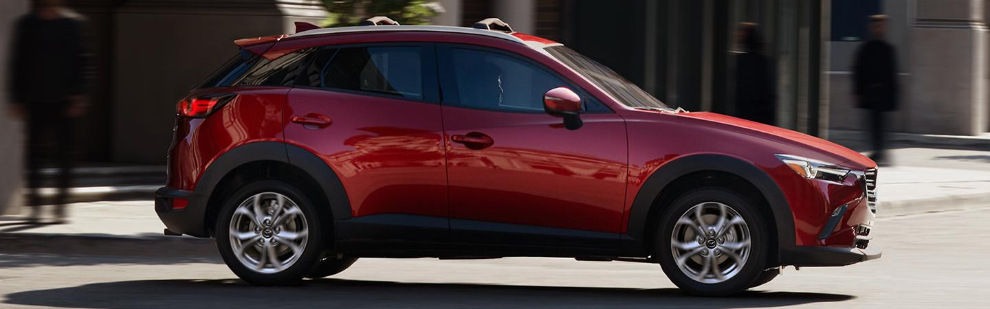 Side profile of a red Mazda CX-3 in motion