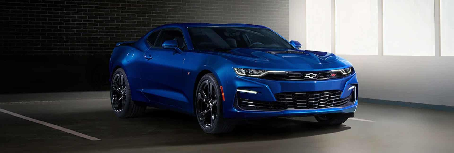 Angled side profile of a parked blue Chevrolet Camaro
