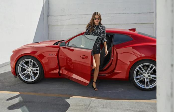 A driver getting out of a parked red Chevrolet Camaro