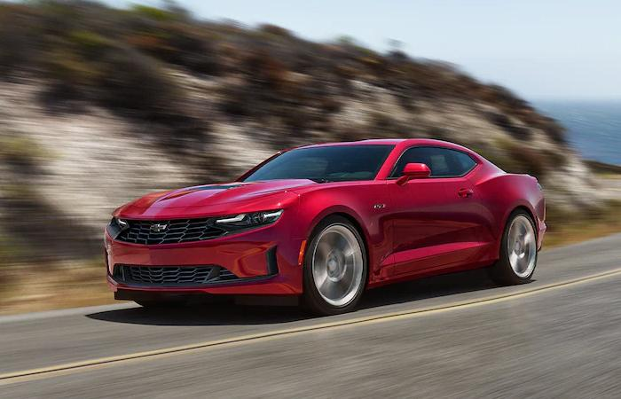 A red Chevrolet Camaro in motion