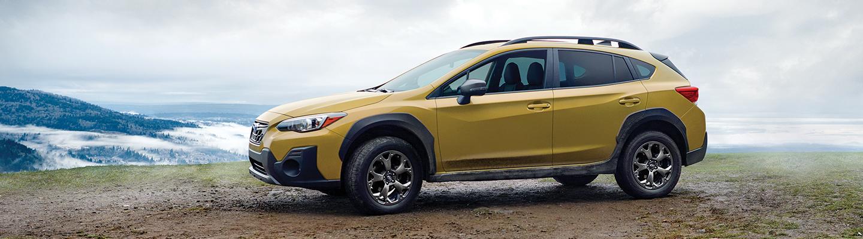 Yellow Subaru Crosstrek parked on hillside overlooking valley