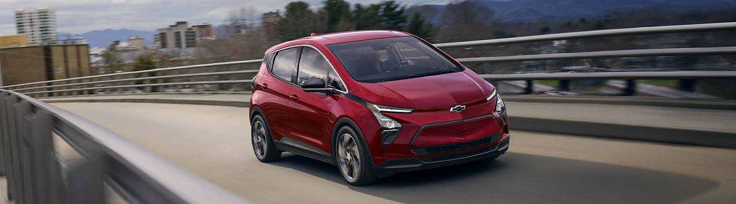 Angled profile of a red electric Chevy vehicle in motion