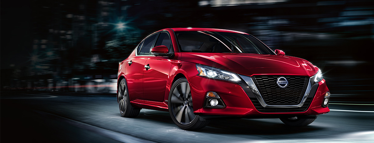 Front view of a red Nissan Altima in motion