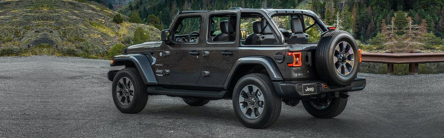Rear driver's side angle of gray Wrangler with tops and doors off