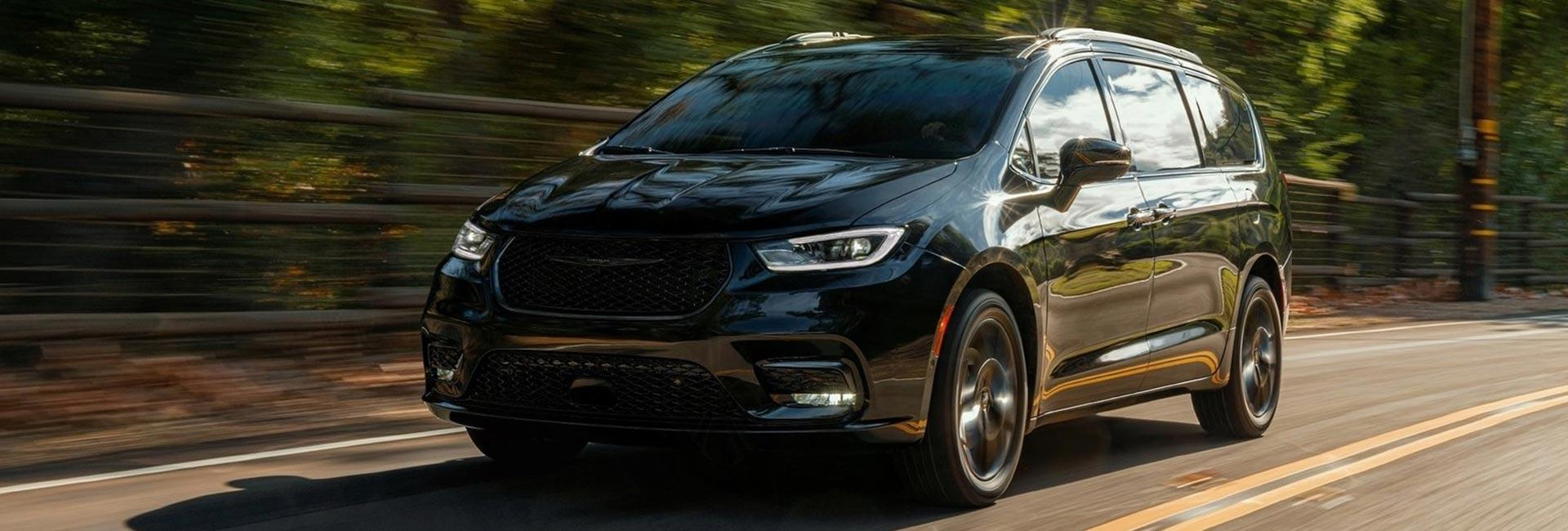 EBlack 2021 Pacifica in motion through a forest road