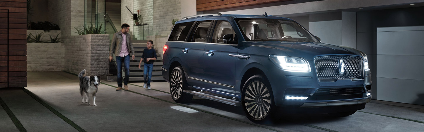 2019 Lincoln Navigator parked next to a dog and family