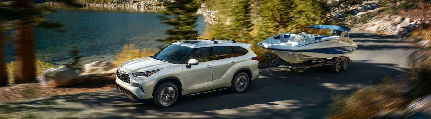 2021 Toyota Highlander Towing a Boat on the Road