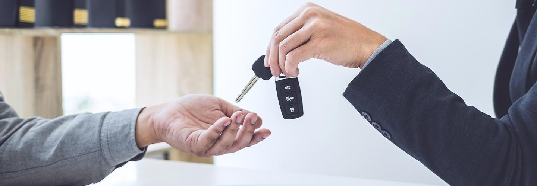 Close up view of a dealership employee handing off car keys