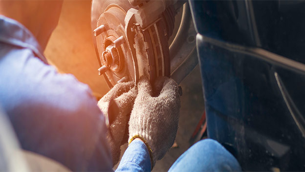 Image of a certified INFINITI mechanic working on the brakes of a vehicle in the Bob Moore INFINITI service department in Oklahoma City