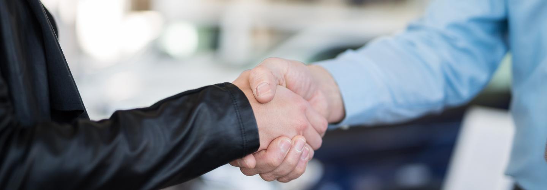 A Hyundai customer and a sales professional shaking hands