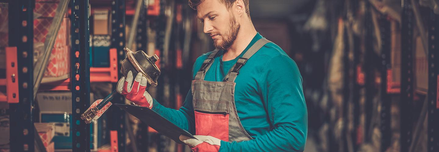 Mechanic Looking at car part in warehouse