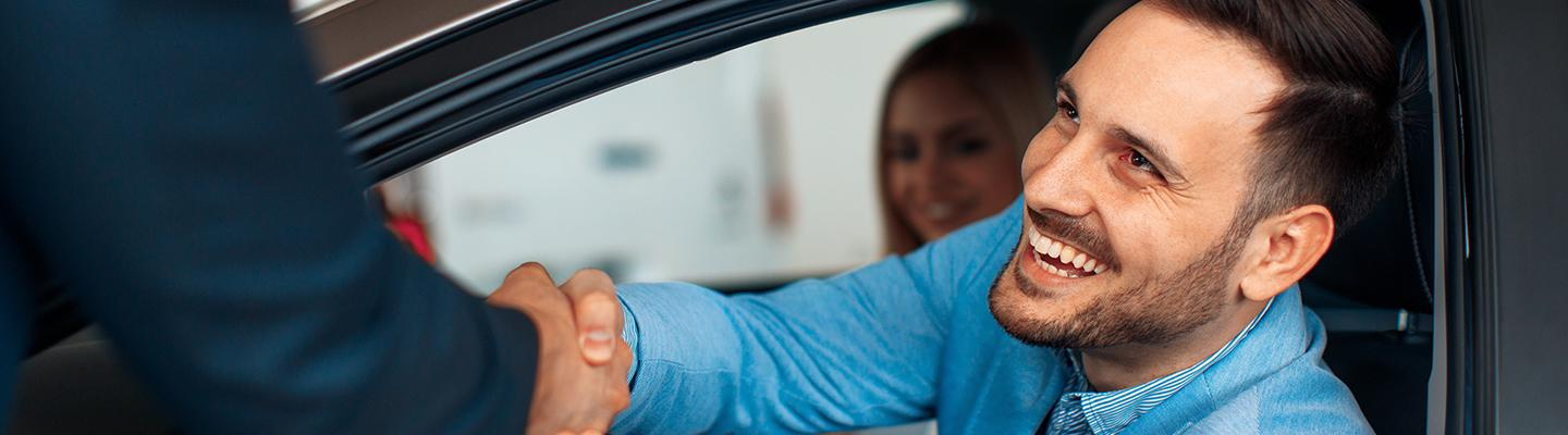 Customer shaking hands after new car purchase.