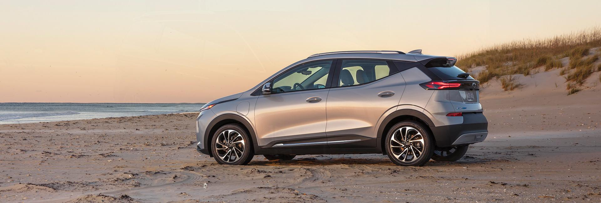 Side profile of a silver Chevy Bolt parked on a beach