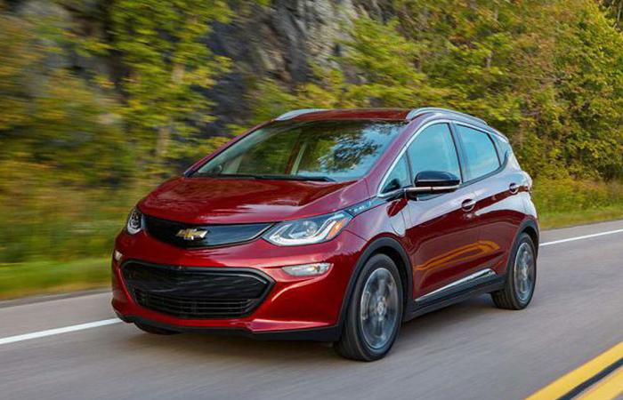Angled front profile of a red Chevy Bolt in motion