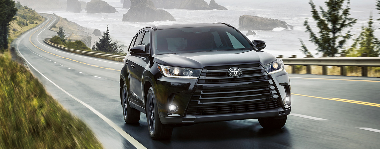 2019 Toyota Highlander Exterior in Black - Driving on the road near the ocean.