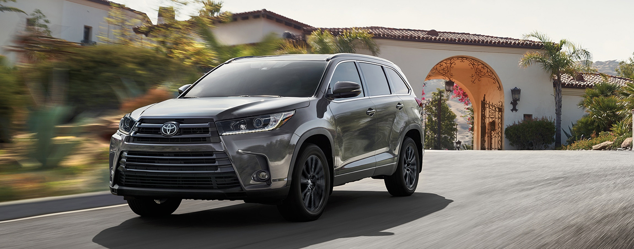 2019 Toyota Highlander Exterior in Gray - Driving on the road near buildings.