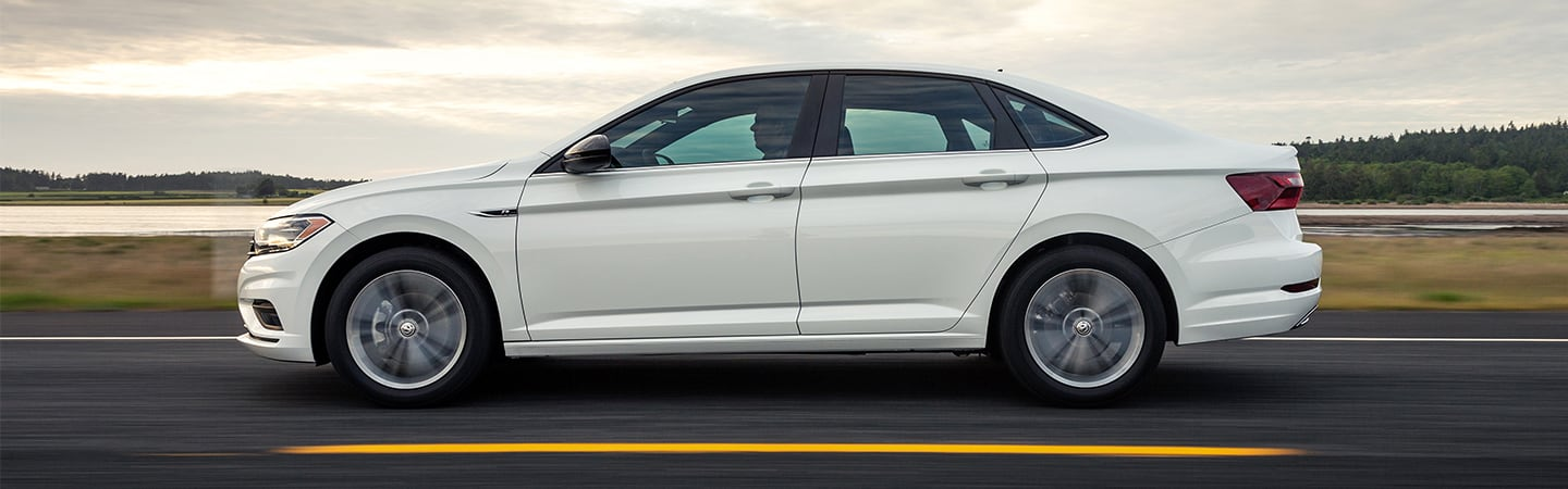Side view of a white 2020 Volkswagen Jetta in motion