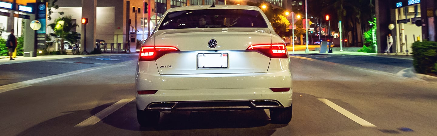 Rear view of a white 2020 Volkswagen Jetta in motion