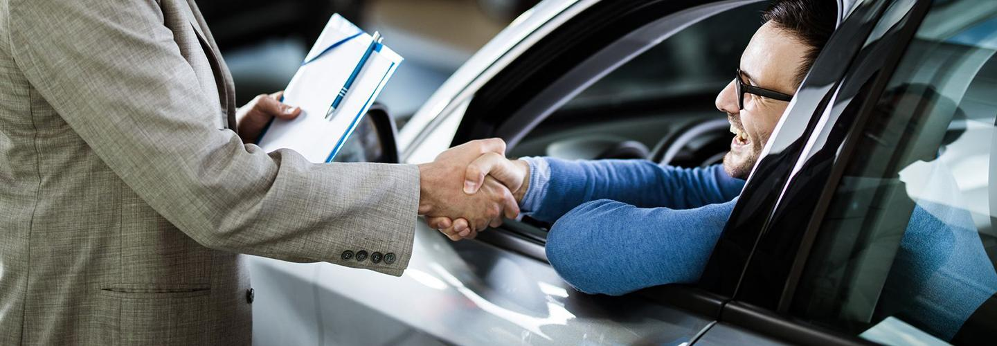 A dealership employee and customer shaking hands