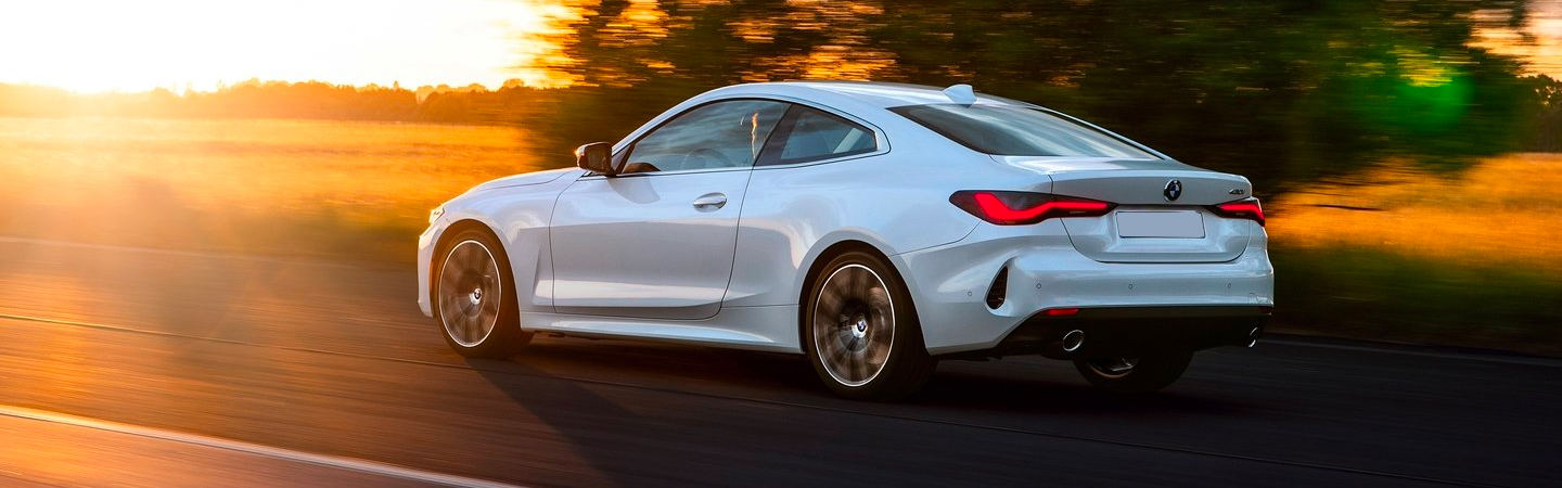 White 2021 BMW 4 Series driving on road during sunset