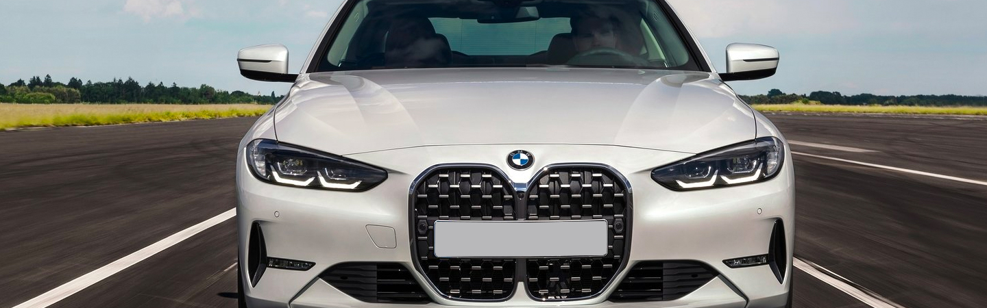Closeup of Grille and windshield of White 2021 BMW 4 Series driving on highway