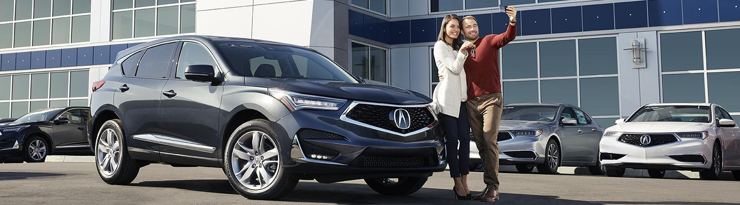 A couple taking a selfie next to their new Acura SUV