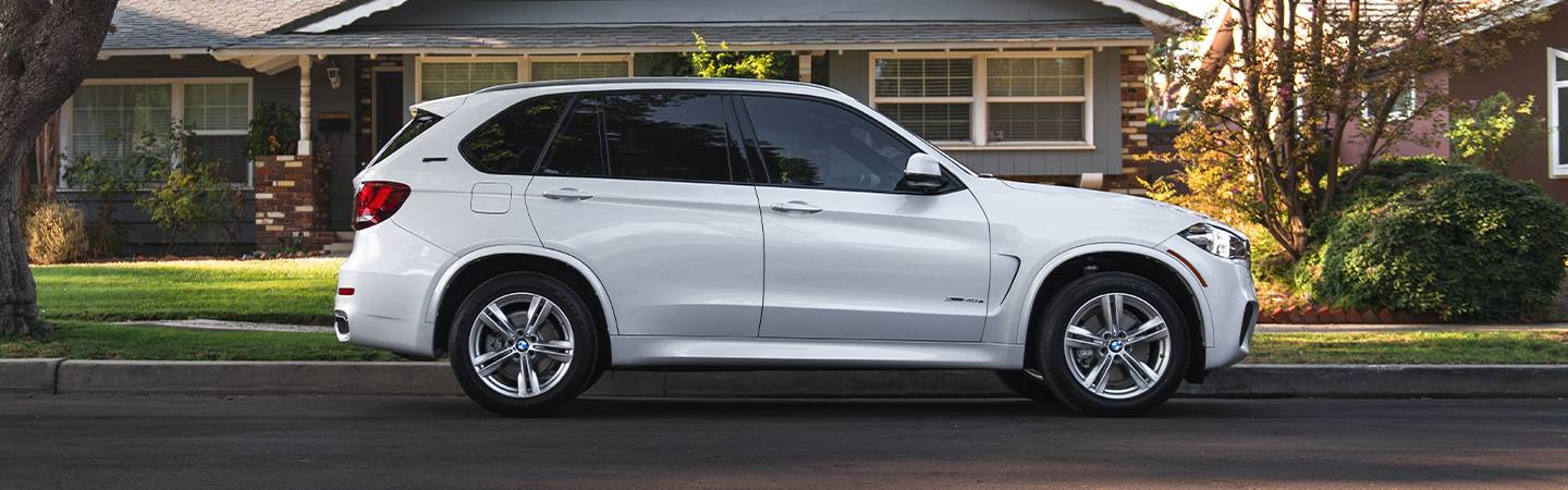 White 2020 BMW X5 driving through a neighborhood