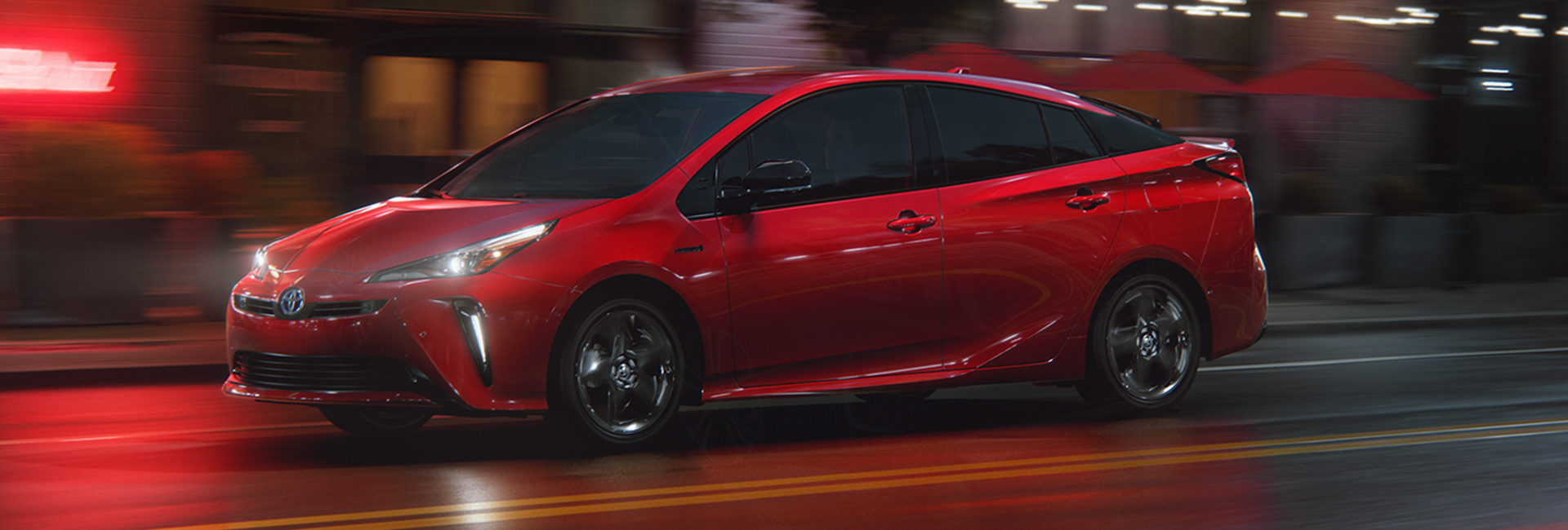 Red 2021 Prius in motion at night