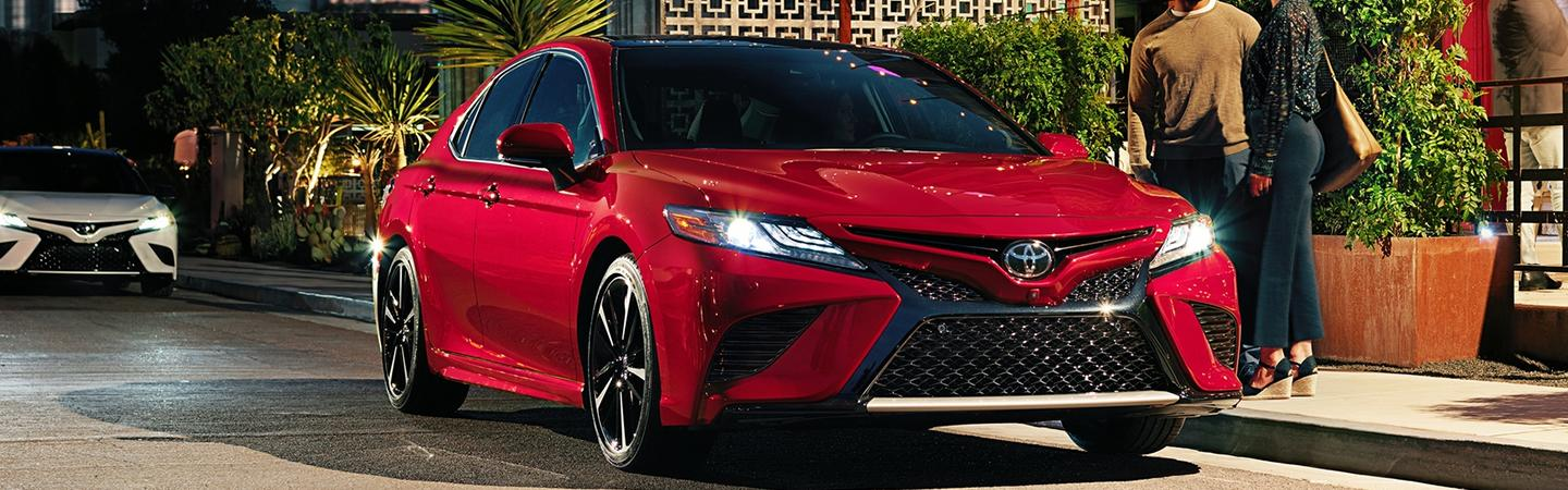 Red and White 2020 Toyota Camrys Parked on Street at Night