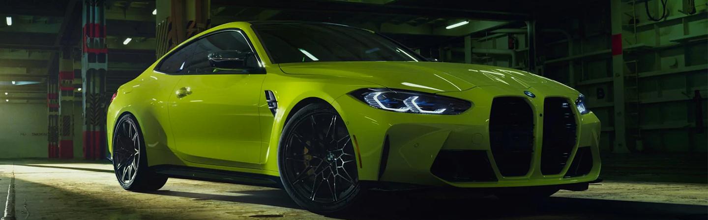 Green 2021 BMW M4 parked in dark garage